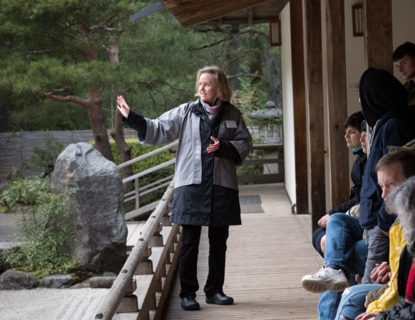 A volunteer in a gray jacket points to something in the Garden while talking to a group on the Pavilion's West Veranda