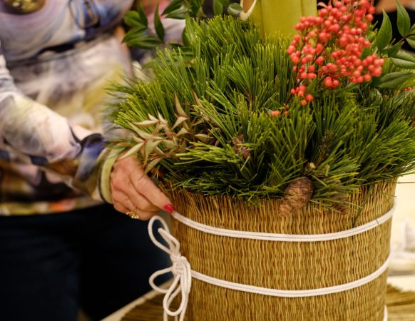 A close up of a kadomatsu decoration and hands, featuring details of berries and pine cones