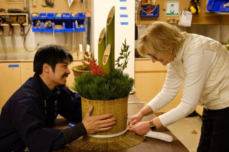 Gardener holds kadomatsu decoration base while student with a smile ties white string around it